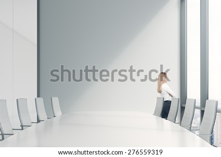 Side view of the young beautiful lady who is looking out the panoramic window in an office. Conference room in a modern office of a consulting company. - stock photo