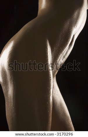 Side view of thighs and stomach of nude Hispanic mid adult woman glistening with body oil. - stock photo