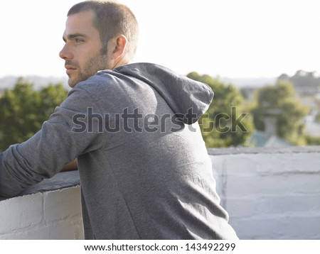 Side view of thoughtful young man leaning on wall looking away - stock photo