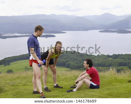 Side view of three joggers relaxing on grassland against lake - stock photo