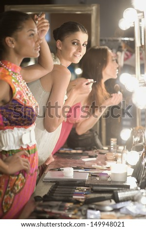 Side view of three multiethnic female models applying makeup in dressing room mirror - stock photo