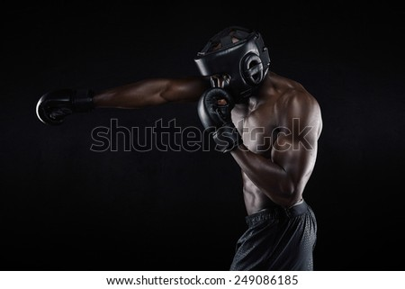 Side view of tough young male boxer practicing on black background. African athlete exercising boxing. Preparing for competition. - stock photo