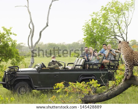 Side view of tourists in jeep looking at cheetah lying on log - stock photo