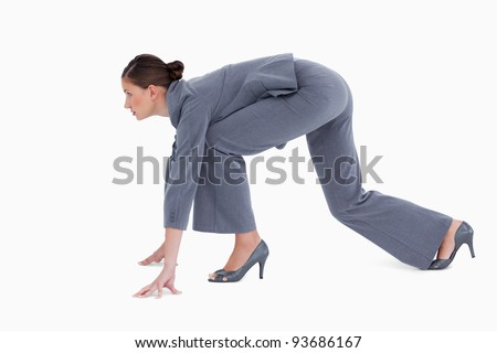 Side view of tradeswoman in sprinting position against a white background