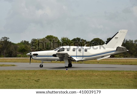 Side view of turboprop airplane on the ground taciing - stock photo
