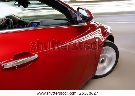 Side view of turning luxury car in motion - stock photo