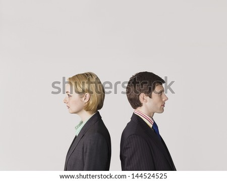 Side view of two business people standing back to back on gray background - stock photo