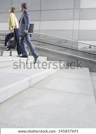Side view of two business people walking up steps outdoors - stock photo