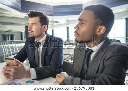 Side view of two businessmen are looking away.