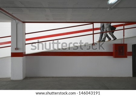 Side view of two businessmen walking down ramp in parking garage with luggage - stock photo