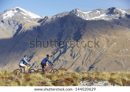 Side view of two cyclists riding past mountains - stock photo