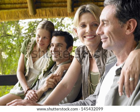 Side view of two happy couples sitting on terrace - stock photo