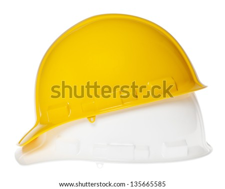 Side view of two hard hats, yellow on top of white, isolated on white background. - stock photo