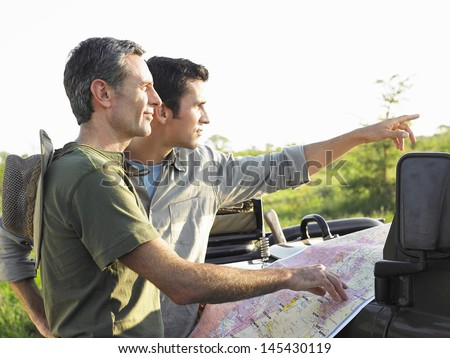 Side view of two male friends with map on bonnet of jeep - stock photo