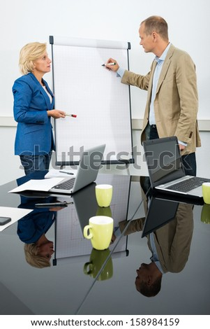 Side view of two managers discussing a diagram on a flipchart in conference room - stock photo