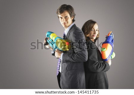 Side view of two smiling businesspeople standing back to back with water guns against gray background - stock photo