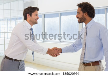 Side view of two smiling young businessmen shaking hands in the office - stock photo