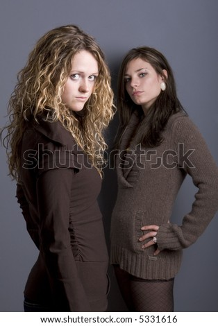 Side view of two teenage girls looking at camera with arrogant expression.