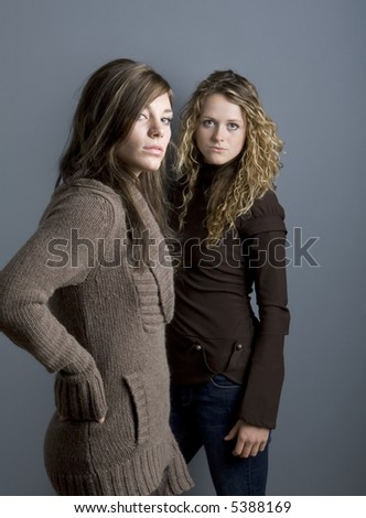 Side view of two teenage girls looking at camera with confident expression. - stock photo