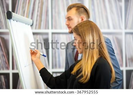 Side view of two young businesspeople working on flipchart at office