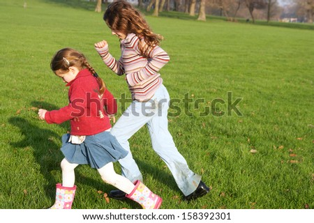 Side view of two young children girls sisters walking fast together across a green grass field in a park during a sunny autumn day, outdoors. - stock photo