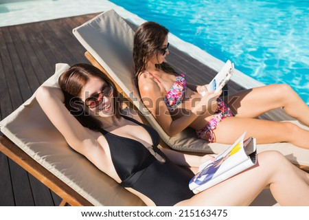 Side view of two young women reading books on sun loungers by swimming pool - stock photo