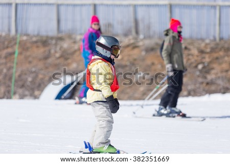 Side view of unrecognizable little boy standing on skis, wearing helmet and snow mask on a ski class - stock photo