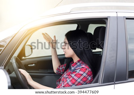Side view of upset young woman at steering wheel, driving car