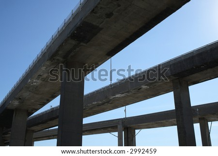Side view of urban highway viaducts against the blue sky. - stock photo