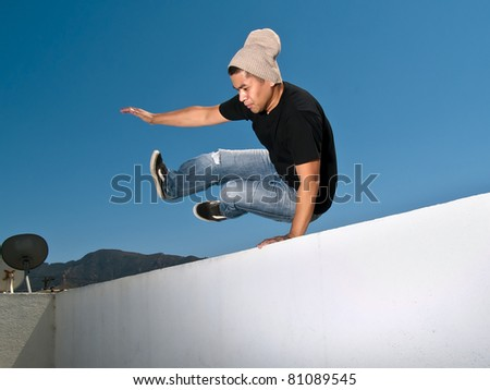 side view of urban parkour free runner jumping over a wall