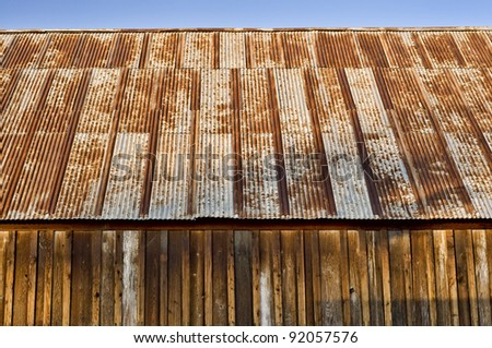 side view of very old wooden barn with rusty roof, a little blue sky at the top