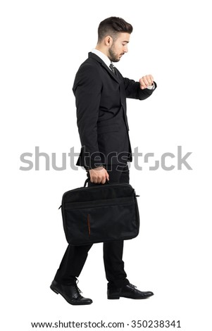 Side view of walking businessman checking hand watch time. Full body length portrait isolated over white studio background. - stock photo