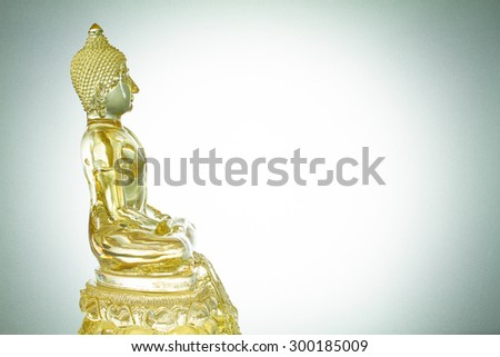 Side view of white mixed with golden transparent glass buddha statue on white background