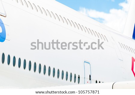Side view of white passenger plane with two rows of windows and blue cloudy sky in background. Place for copy. - stock photo