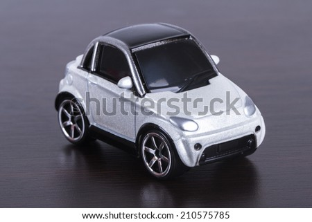 Side view of white, toy, small car on wooden table.