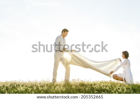 Side view of woman and man spreading picnic blanket on grass during sunny day - stock photo