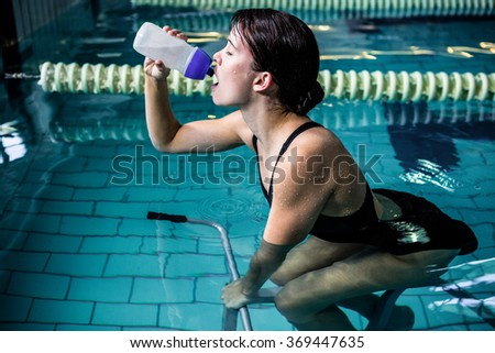 Side view of woman cycling in the pool while drinking water - stock photo