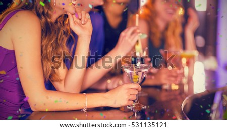 Side view of woman having glass of cocktail in bar against flying colours