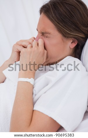 Side view of woman in hospital bed sneezing - stock photo