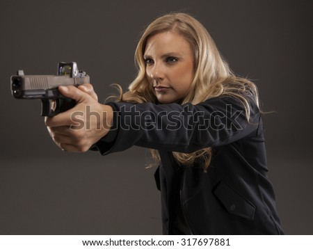 Side view of woman pointing a gun. REFUSE TO BE A VICTIM. - stock photo