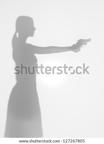 side view of woman silhouette holding a handgun aiming in front of her, behind a diffuse surface - stock photo
