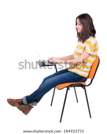 Side view of  woman sitting on a chair to study with a laptop. Isolated  over white background - stock photo