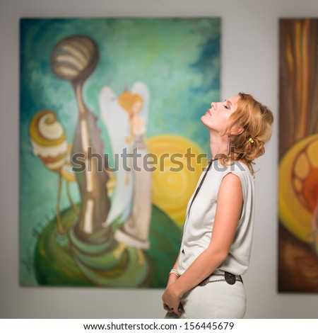 side view of woman standing in an art gallery with her eyes closed and her head facing up - stock photo