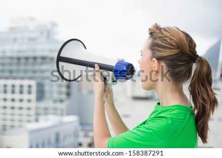 Side view of woman using and screaming in megaphone - stock photo