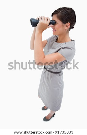 Side view of woman using spyglasses against a white background