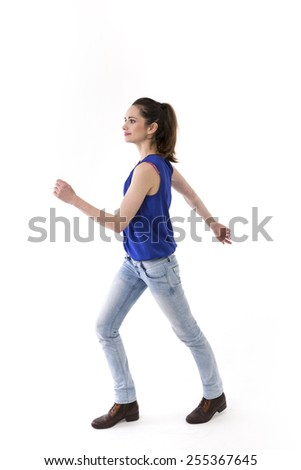 Side view of woman walking, wearing blue jeans and casual top. Full length image, isolated on white. - stock photo