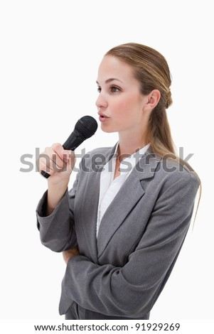 Side view of woman with microphone against a white background - stock photo