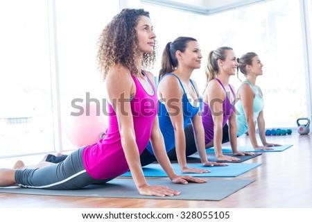 Side view of women doing cobra pose in fitness studio - stock photo