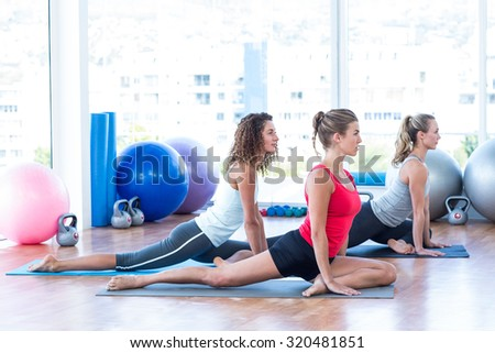 Side view of women doing pigeon pose in fitness studio - stock photo