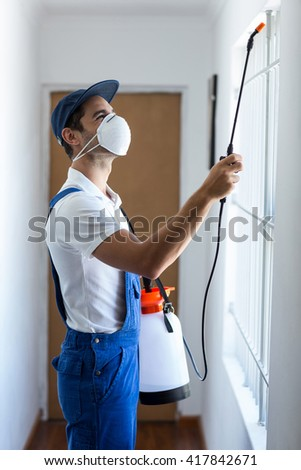 Side view of worker using pesticide on window at home - stock photo
